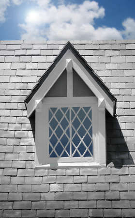 second floor: Small window on second floor of old home with blue sky and cloud Stock Photo