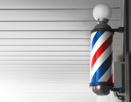 Old fashioned vintage barber shop pole against modern background photo