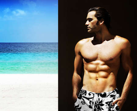 Outdoor portrait of a gorgeous male fitness model at the beach looking away