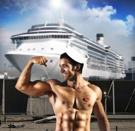 heart tattoo: Sexy male model as sailor flexing his bicept in front of ship at port with a heart tattoo on his chest