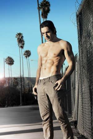 young male model: Retrato de moda de al aire libre joven modelo masculino sin camisa en entorno urbano