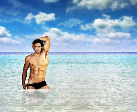 macho: Portrait of a fit muscular male model standing in clear warm tropical waters with lots of copy space Stock Photo