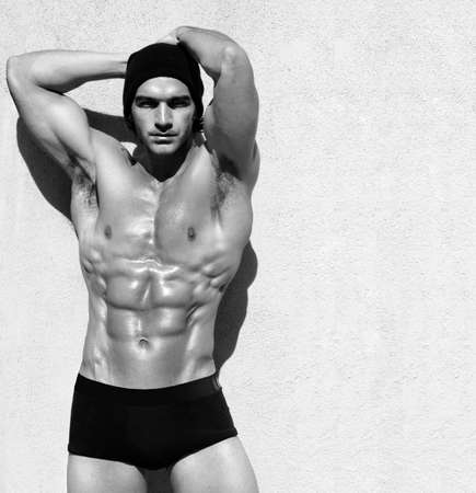 six pack abs: Sexy fine art black and white portrait of a very muscular shirtless male model posing with arms up