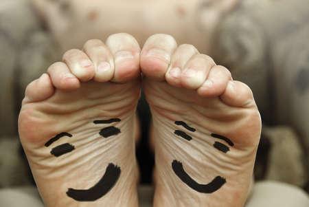 pies masculinos: Imagen divertida de un par de pies desnudos masculinos con feliz cara sonriente dibujada en el fondo