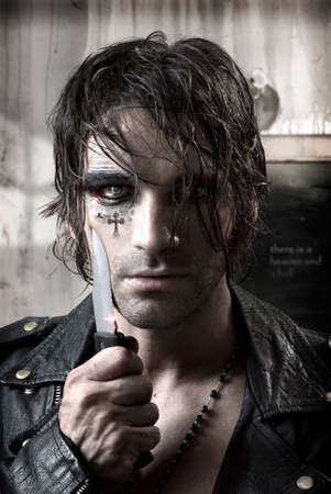 Sexy portrait of a dangerous man holding knife with fashion makeup on face  photo