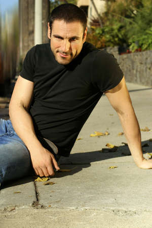 Outdoor portrait of a casual relaxed man leaning on sidewalk photo