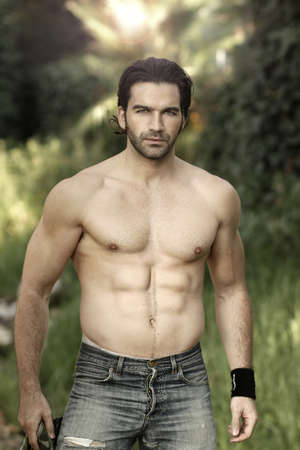 male: Portrait of a hunky male fitness model shirtless in beautiful outdoor natural setting