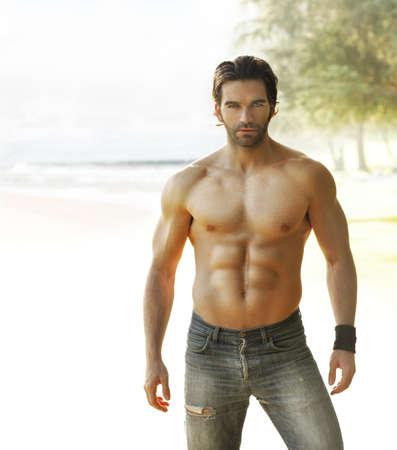 hombres musculosos: Retrato de un hombre sin camisa en jeans hermosa relajarse en el exterior