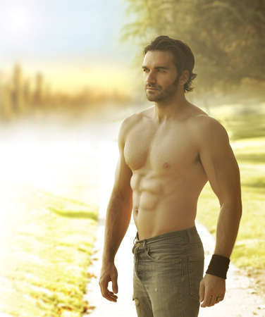males only: Portrait of a beautiful shirtless man in jeans against the light in natural outdoor setting