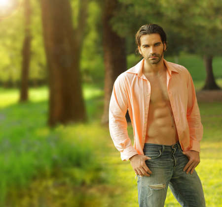 Beautiful male model with open shirt in outdoor setting Stock Photo