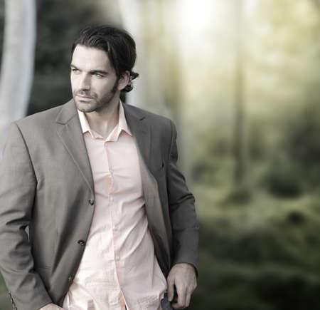 modelos hombres: Retrato de hombre elegante al aire libre en traje con un mont�n de espacio de la copia