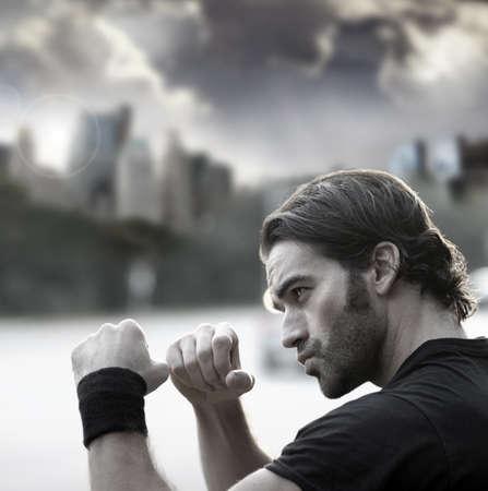 Retro gestileerde foto van een jonge sexy man met vuisten klaar om te vechten tegen de stad achtergrond en dramatische lucht
