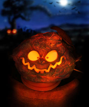 Spooky Halloween image of a glowing jackolantern with eerie night sky in background including moon and bats photo