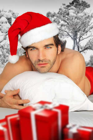 Sexy man in santa cap relaxing in bed with fantastical winter background and red wrapped gifts in foreground photo