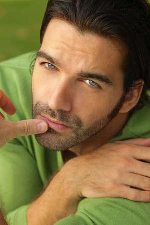 modelos hombres: Close-up retrato de un modelo masculino atractivo, con la expresi�n facial en el jersey verde y el fondo verde