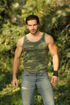 Portrait of a relaxed casual muscular young man in beautiful natural setting  photo