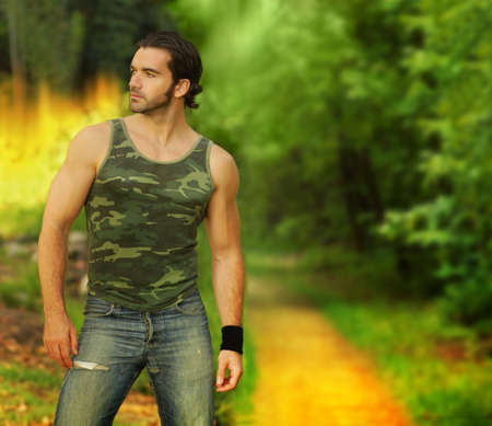 Portrait of a relaxed muscular young man in beautiful natural setting wearing a camouflage tanktop  photo
