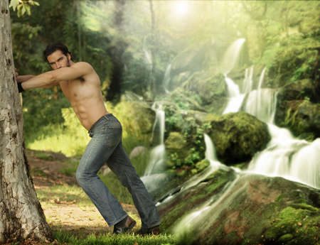 Portrait of a beautiful young muscular man leaning againt a tree in a beautiful, heavenly place photo