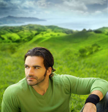 male model: Portrait of a relaxed good-lookiing young man in beautiful natural setting wearing a green sweater