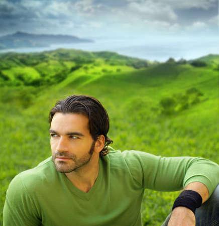 Portret van een ontspannen goed lookiing jonge man in een prachtige natuurlijke omgeving draagt een groene trui