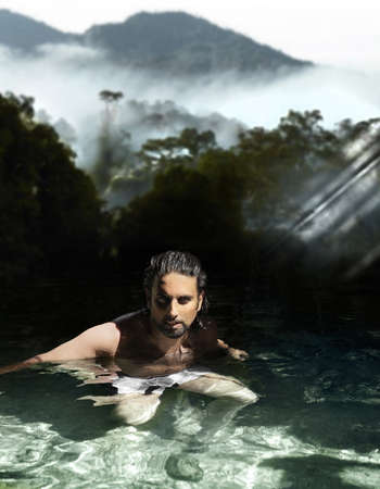 Man bathing in tropical waters with beautiful forests and mountain in the background photo