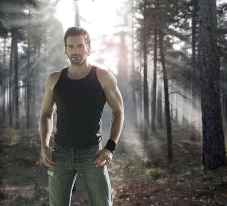 극적인 숲에서 좋은 찾고 남성 모델의 초상화 뒤에 빛의 광선 스톡 콘텐츠