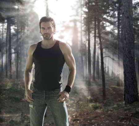 Portrait of a good looking male model in dramatic forest with rays of light behind
