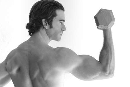 young man lifting weights in black and white photo