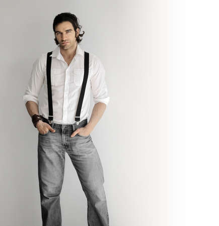 Portrait of a stylish youngman in white shirt and suspenders against white background