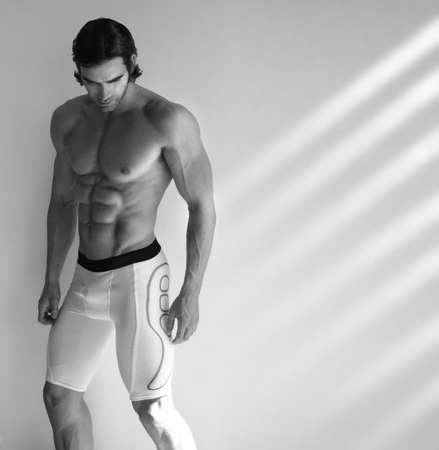 Sexy black and white portrait of young muscular male fitness model in underwear with window light streaming in photo