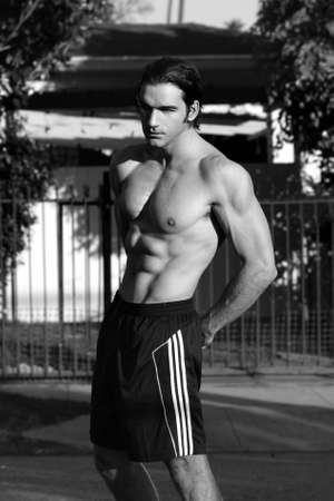 Outdoor black and white portrait of a shirtless good looking fit male model  photo
