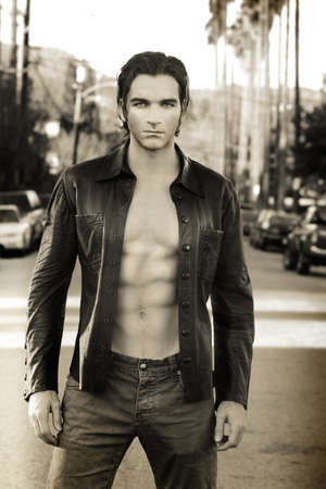 Sepia toned fashion portrait of an edgy male model wearing leather jacket and shirtless outdoors