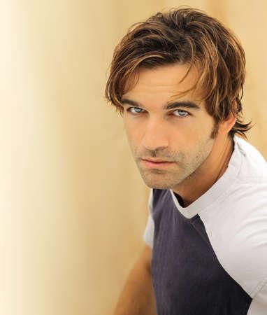 경향: 눈에 띄는 파란 눈을 가진 캐주얼에 어울리는 남성 모델의 초상화