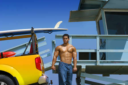 Hot hunky lifeguard on beach with truck and lifeguard stand photo