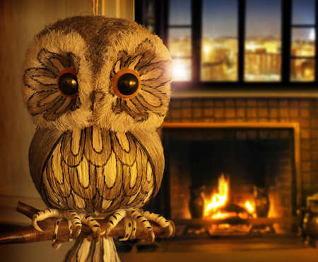 Hand-crafted fake owl perched on a branch in an inviting warm home setting with big window and glowing fireplace photo
