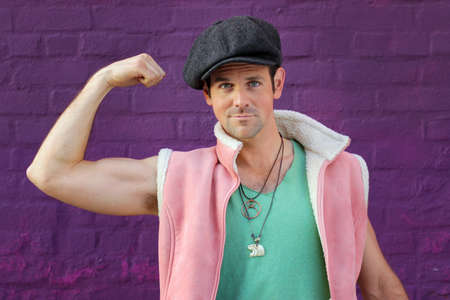 cocky: Portrait of a funny man in green vest, hat, and pink tank flexing his muscle against a vibrant wall Stock Photo