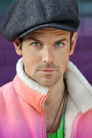 cocky: Portrait of a funny man in green vest, hat, and pink tank against a vibrant wall  Stock Photo