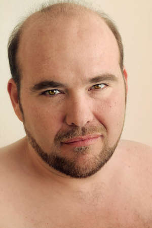 Detailed closeup portrait of a mature balding man with beard against warm neutral background Фото со стока