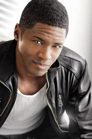 mannequin africain: Portrait d'un jeune homme en veste de cuir noir sur un fond lumineux et moderne