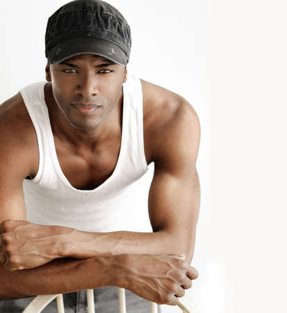 Portrait of a cool young man leaning on chair in white tank and trendy cap against neutral background photo