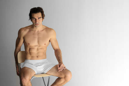 Gorgeous young muscular male model in underwear sitting on stool against neutral background photo