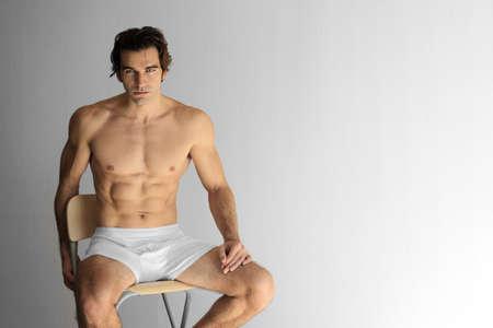 ropa interior: Hermosa joven modelo musculoso hombre en ropa interior sentada en el taburete contra el fondo neutro Foto de archivo