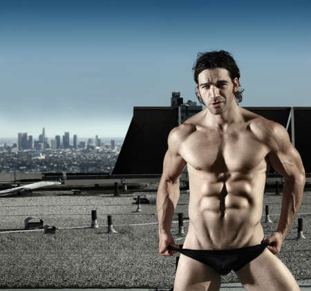 Fashion portrait of sexy male model in black briefs on top of roof with city in background Banco de Imagens