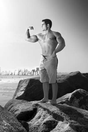 Outdoor black and white portrait of a young muscular man flexing on top of rocks with city skyline in background photo