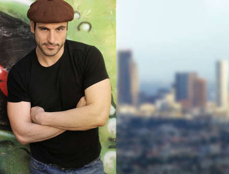 cool guy: Portrait of a casual man leaning on wall with city in background