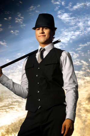smirk: Young confident man in top hat and cane against beautiful sky background
