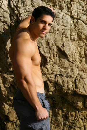 body built: Young bodybuilder shirtless against rocks turning toward viewer Stock Photo