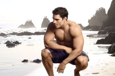 Young, ajustement beau homme torse nu sur la plage