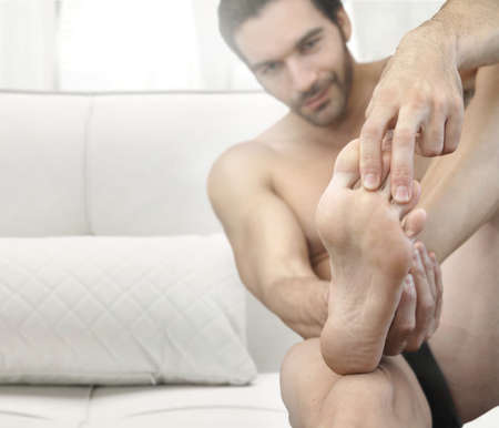 adult's feet: Portrait of a man in bed looking at his feet with focus on the foot Stock Photo