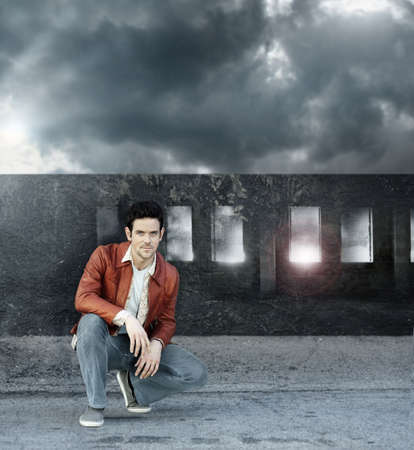 Stylized fashion portrait of a young man kneeling in front of a decaying grungy bridge with dramatic cloudscape